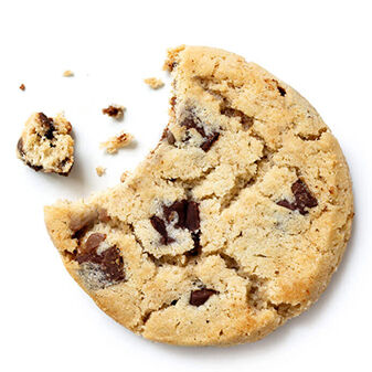 Light chocolate chip cookie, bite missing with crumbs from above.